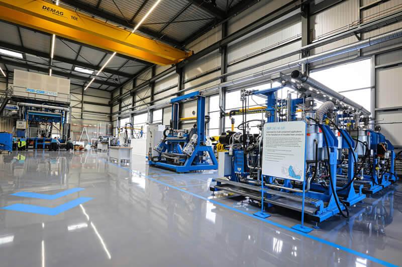 Bessere Ausnutzung und kürzere Wege innerhalb der rund 1000 Quadratmeter großen Halle. Im Vordergrund: 6-Komponenten-Hochdruckdosiermaschine mit 40-t-Formenträger.